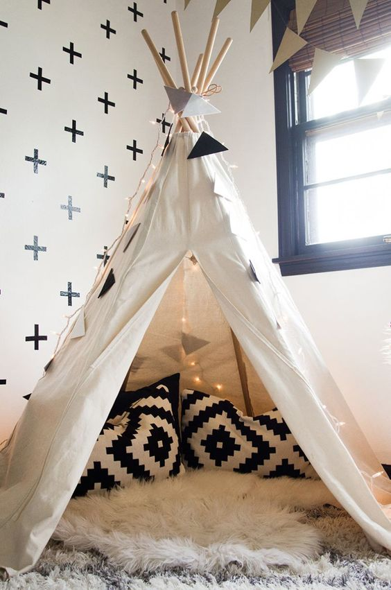 A teepee in a child's bedroom filled with cushions and sheepskin rugs as