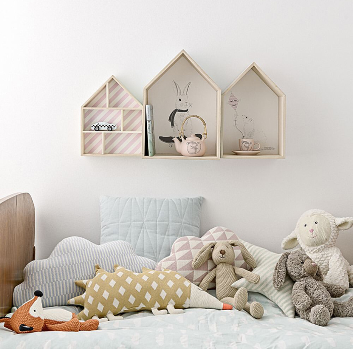 A child's bedroom filled with soft toys and pastel coloured soft furnishings