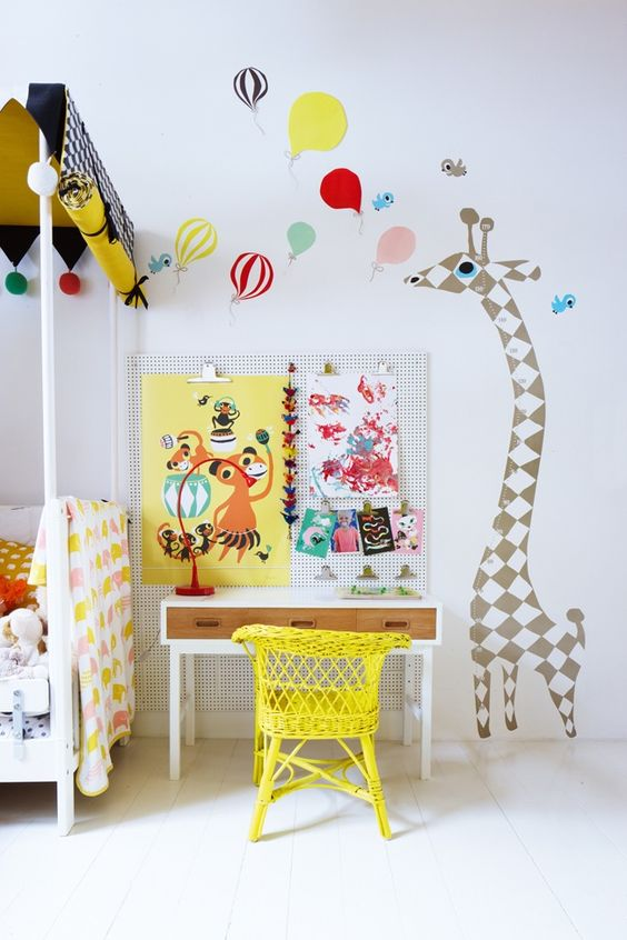 A children's bedroom with brightly coloured wall decals in balloon and giraffe shapes.Blank walls can be a canvas for bright, fun, inspirational decor