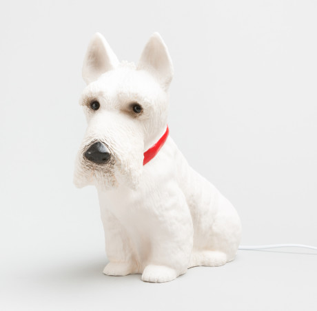 A bedside lamp in the shape of a white scotty dog