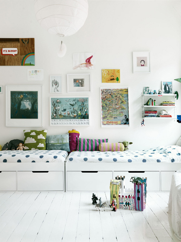 A child's room with picture on the wall and a bed that doubles as storag