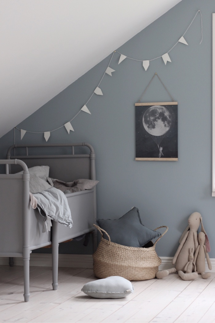 A child's bedroom with a grey wall and a hanging moon print