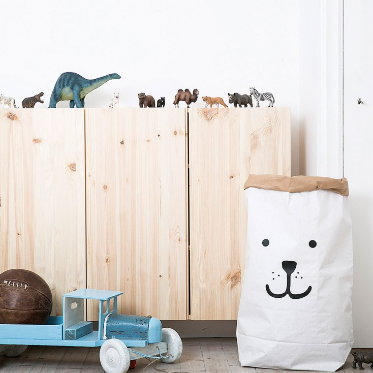 A paper storage bag with a smiley face on it in a kids' room