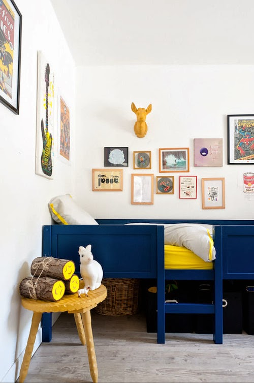 A children's bedroom with art on the walls of all different shapes and sizes