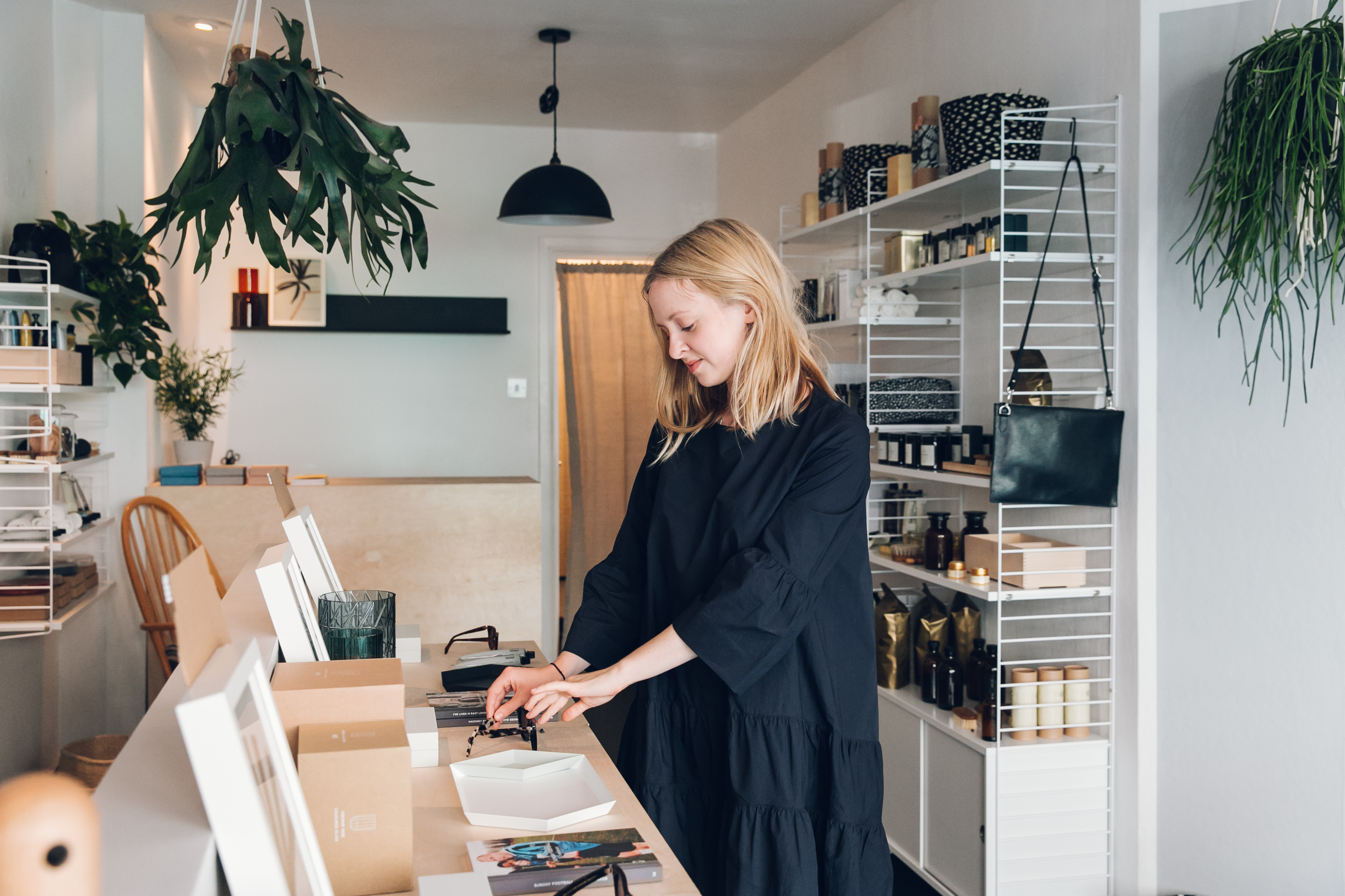 Shop assistant arranging objects in an independent shop