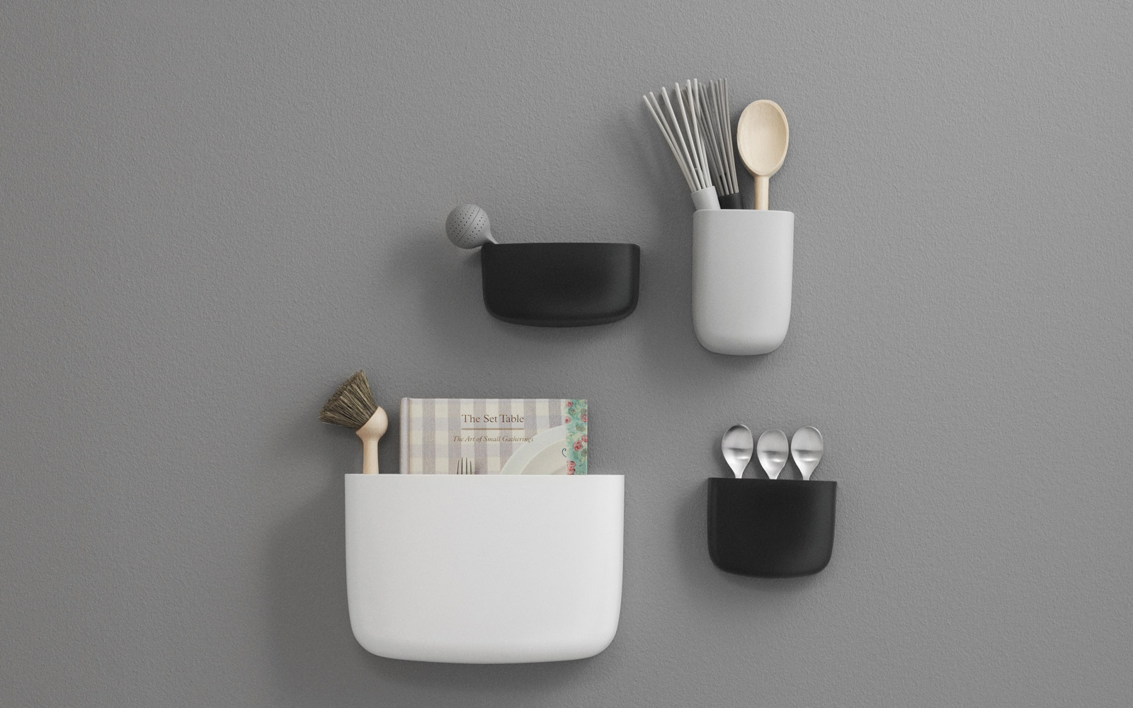 Minimal white, grey and black storage pots displayed against a grey wall. The storage pots vary in size and are filled with common kitchen items.