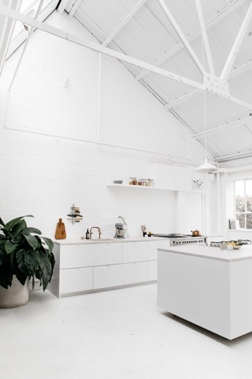 A contemporary minimalist kitchen featuring a white colour pallet, high ceilings, natural light, beams and minimal clutter.