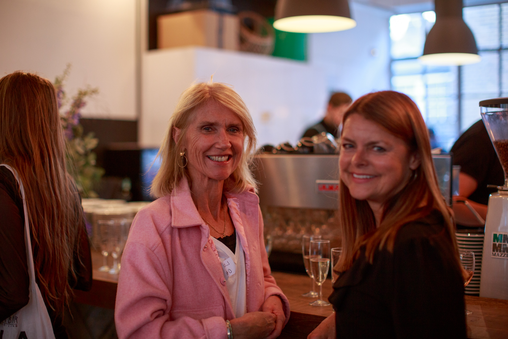 Two guests stand next to the prosecco bar smiling at the camera.